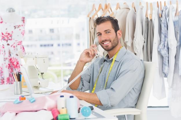 Portret młody męski projektant mody używa telefon