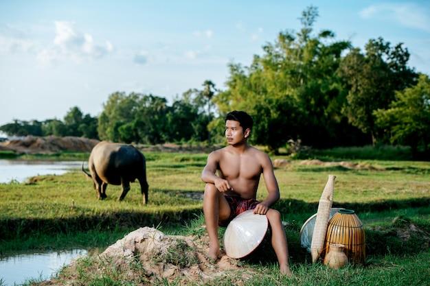 Portret młody mężczyzna topless noszący przepaskę biodrową w wiejskim stylu życia siedzący z bambusową pułapką wędkarską