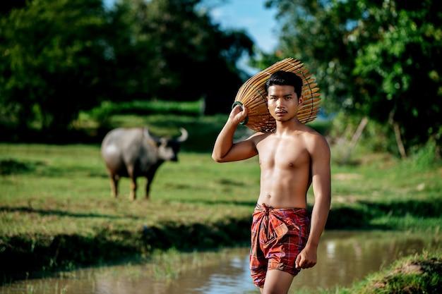 Portret młody mężczyzna topless używa bambusowej pułapki wędkarskiej do łapania ryb do gotowania