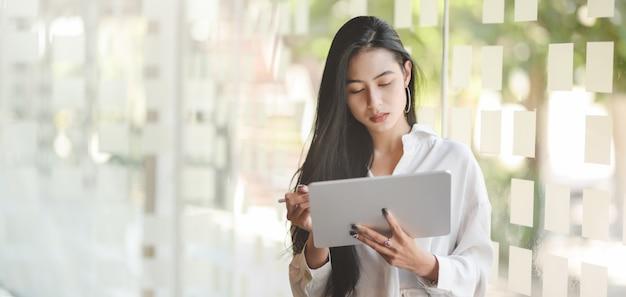 Portret młody namiętny azjatykci bizneswoman używa cyfrową pastylkę podczas gdy stojący w nowożytnym biurze