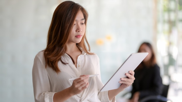 Portret młody piękny azjatykci bizneswoman pracuje na jej projekcie podczas gdy używać pastylkę w nowożytnym biurze