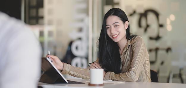 Portret młody piękny bizneswoman pracuje nad jej projektem podczas gdy ono uśmiecha się kamera