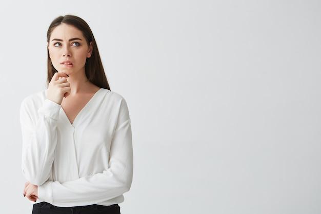 Portret młody piękny brunetka bizneswoman marzy myślący marszczący brwi. dłoń na brodzie.