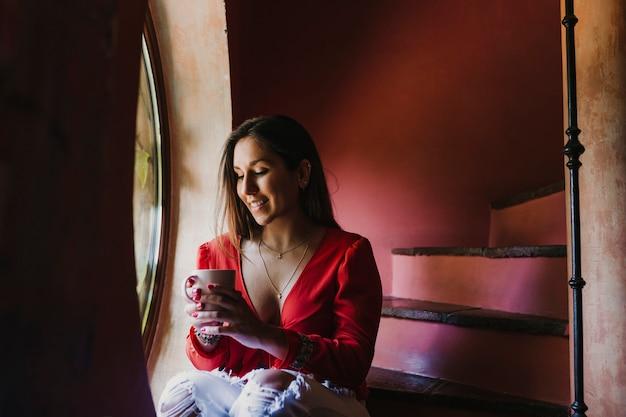 Portret młody piękny kobiety obsiadanie okno relaksował w domu trzymać filiżankę herbata kawy. styl życia w pomieszczeniu