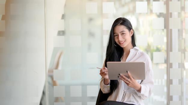 Portret młody piękny projektant grafik komputerowych pracuje nad jej projektem z pastylką i patrzeje kamerę podczas gdy stojący w nowożytnym biurze