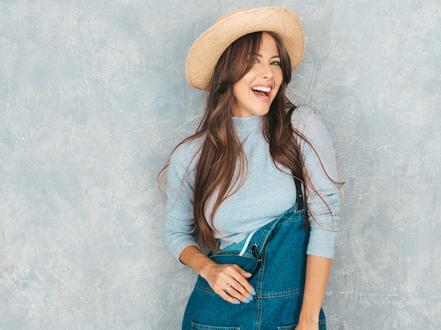 Portret młody piękny uśmiechnięty kobiety patrzeć. modna dziewczyna w swobodnym letnim kombinezonie ubrania i kapelusz.