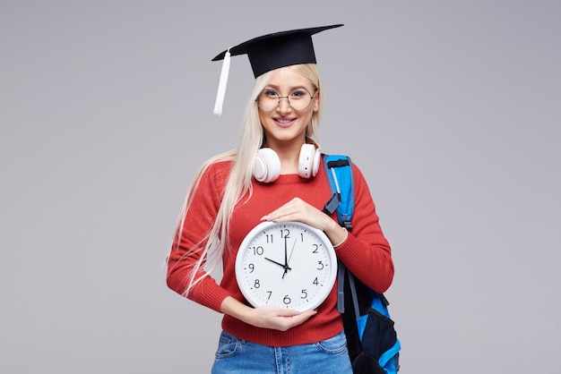 Portret młody podekscytowany blond kobieta uczeń w magisterskiej nakrętce z plecakiem trzyma dużego budzika odizolowywającego na szarości przestrzeni. edukacja na studiach. skopiuj miejsce na tekst
