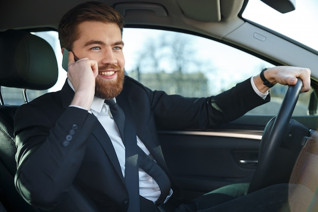 Portret młody przystojny biznesowy mężczyzna opowiada na telefonie