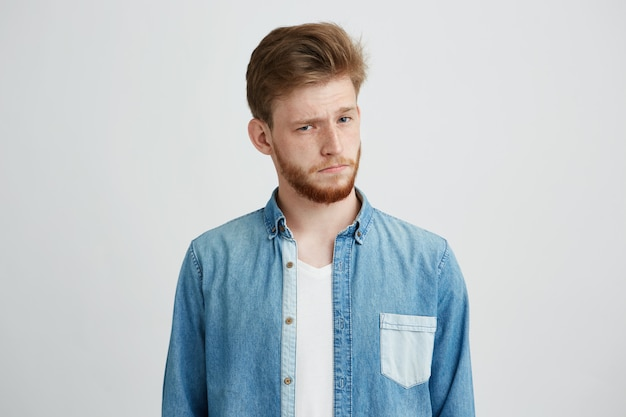 Portret młody przystojny mężczyzna w cajgowej koszula podnosi up brew patrzeje kamerę.