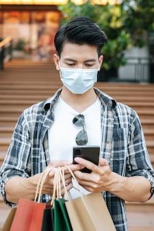 Portret młody przystojny mężczyzna w masce ochronnej trzyma papierową torbę