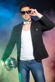Portret młody przystojny mężczyzna z lustrzaną piłką.