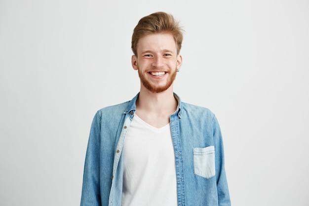Portret młody przystojny modnisia mężczyzna uśmiecha się śmiać się z brodą.