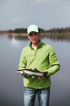 Portret młody rybak trzyma świeżej złapanej ryba