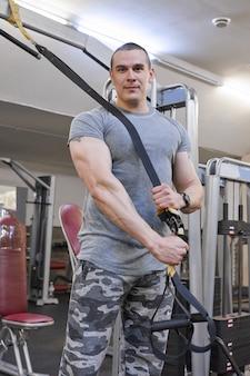 Portret młody silny uśmiechnięty mięśniowy uśmiechnięty mężczyzna w gym