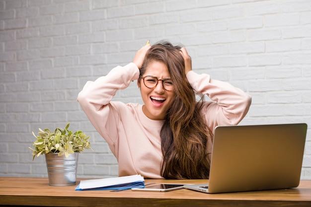 Portret młody studencki łaciński kobiety obsiadanie na jej biurku udaremniający i desperacki
