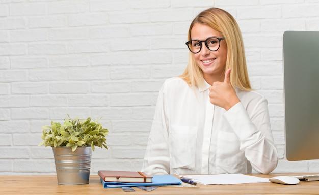 Portret młody studencki obsiadanie na jej biurku robi zadaniom rozochoconym i excited.