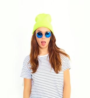 Portret młody stylowy kobieta model w przypadkowych letnich ubraniach w żółtym beanie kapeluszu odizolowywającym na bielu. pokazując jej język