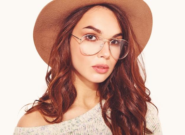 Portret młody stylowy model w przypadkowych letnich ubraniach w brown kapeluszu z naturalnym makeup w szkłach na bielu