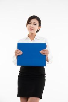Portret młody szczęśliwy azjatykci bizneswoman ręki ręki chwyta raportu dokument odizolowywający nad biel ścianą