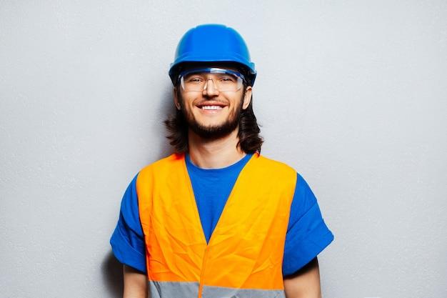 Portret młody szczęśliwy pracownik budowlany jest ubranym sprzęt ochronny; niebieski kask, przezroczyste okulary