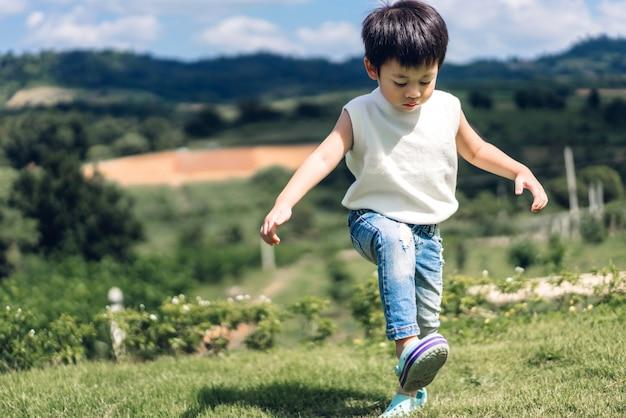 Portret młody szczęśliwy śliczny chłopiec dziecko cieszy się i bawić się w naturze