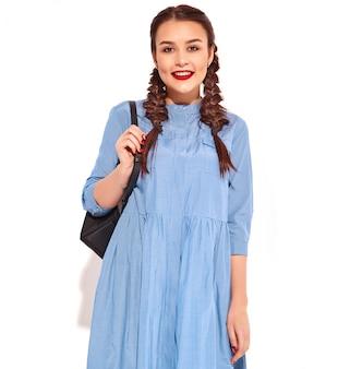 Portret młody szczęśliwy uśmiechnięty kobieta model z jaskrawym makeup i czerwonymi wargami z dwa warkoczami w rękach w lato błękita kolorowej sukni i plecaku odizolowywających