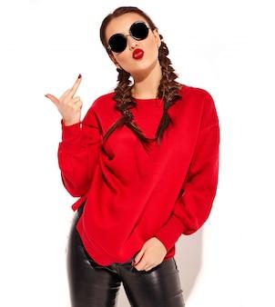 Portret młody szczęśliwy uśmiechnięty kobieta model z jaskrawym makeup i kolorowymi wargami z dwa warkoczami i okularami przeciwsłonecznymi w lato czerwieni ubraniach odizolowywających. pokazując kurwa znak