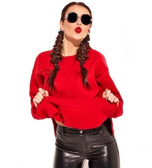 Portret młody szczęśliwy uśmiechnięty kobieta model z jaskrawym makeup i kolorowymi wargami z dwa warkoczami i okularami przeciwsłonecznymi w lato czerwieni ubraniach odizolowywających.