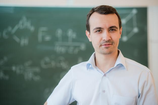 Portret młody szczęśliwy uśmiechnięty nauczyciela lub ucznia mężczyzna stoi blisko chalkboard