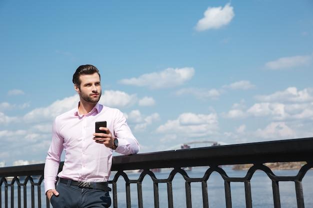 Portret młody ufny mężczyzna używa smartphone blisko rzeki