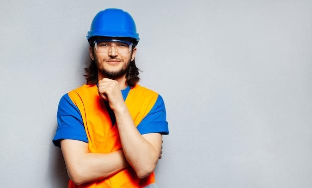 Portret młody ufny pracownik budowlany jest ubranym sprzęt ochronny; niebieski kask, przezroczyste okulary