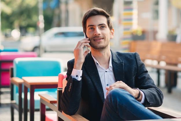 Portret młody uśmiechnięty biznesmen opowiada na telefonie