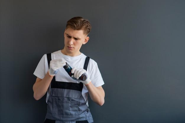 Portret młody uśmiechnięty pracujący mężczyzna w szarych kombinezonach. pracownik trzyma elektrycznego świder na szarym tle