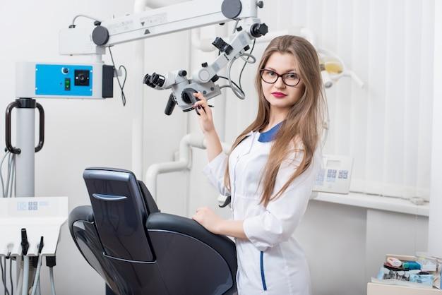 Portret młody żeński dentysta przy nowożytnym stomatologicznym biurem