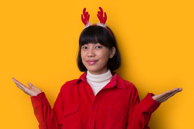 Portret młodych azjatyckich kobiet noszą świąteczny kapelusz z punktem ręki na pustej przestrzeni