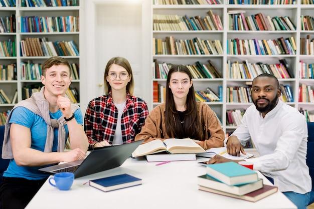 Portret młodych czterech studentów grupy wielorasowe siedzi przy stole z książkami i laptopem, studiując razem w bibliotece uniwersyteckiej