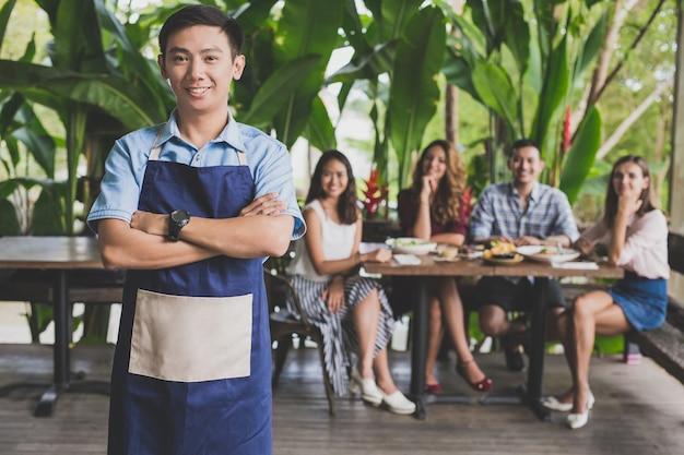 Portret młodych kelnerów, uśmiechniętych i stojących z skrzyżowanymi ramionami przed klientami