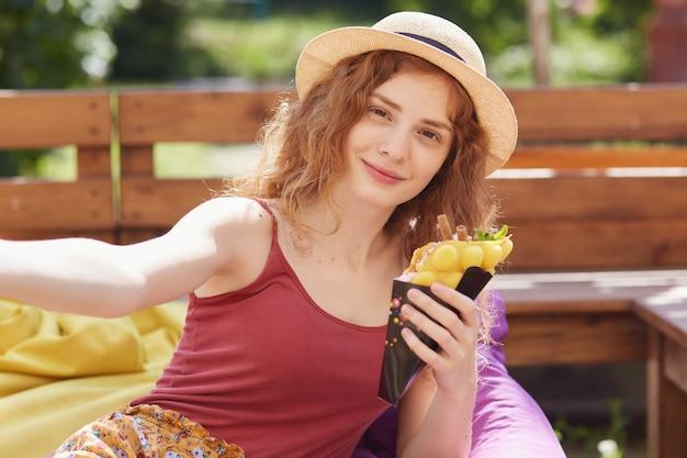Portret młodych kobiet siedzi na świeżym powietrzu na bezramowym krześle, je lody i bierze selfie fotografię w lato parku, relaksuje po zdaniu egzaminów na uniwersytecie, w eleganckich ubraniach i kapeluszu.