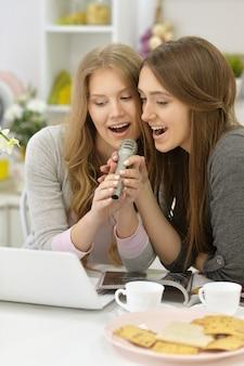 Portret młodych kobiet z mikrofonami i laptopem