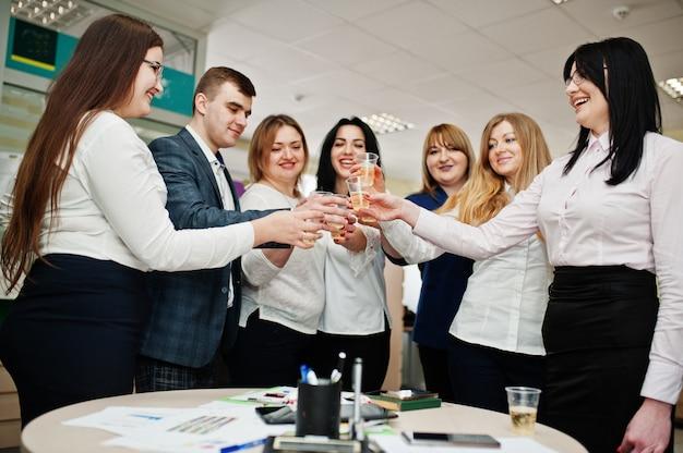 Portret młodych ludzi biznesu grupa pracowników banku w nowoczesnym biurze picia szampana po ciężkim dniu pracy.