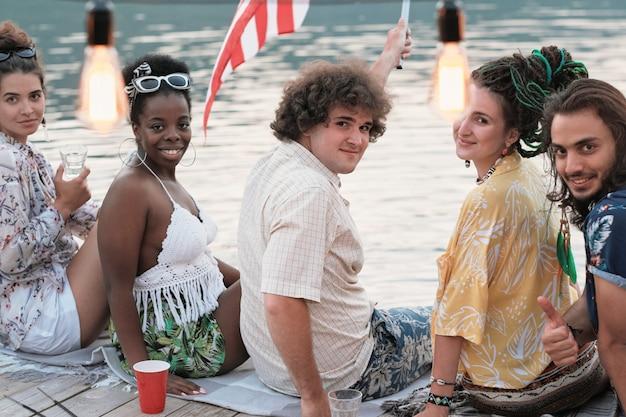 Portret młodych ludzi siedzi na molo i uśmiecha się do kamery, są na imprezie