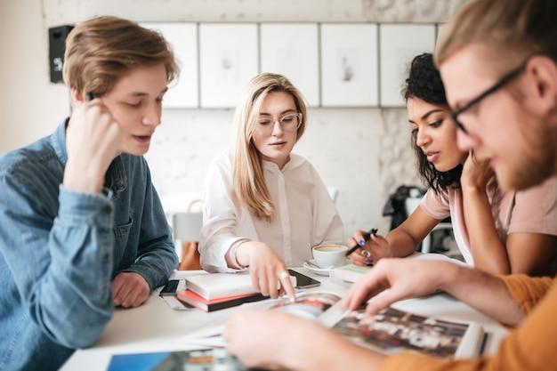Portret młodych ludzi w zamyśleniu omawiających czasopisma w biurze.