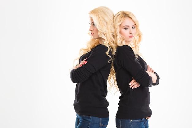Portret młodych obrażonych sióstr bliźniaków stojących plecami do siebie na białym tle na białym tle