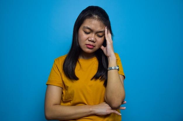 Portret młodych pięknych azjatyckich kobiet z niebieskim na białym tle gestem bólu głowy