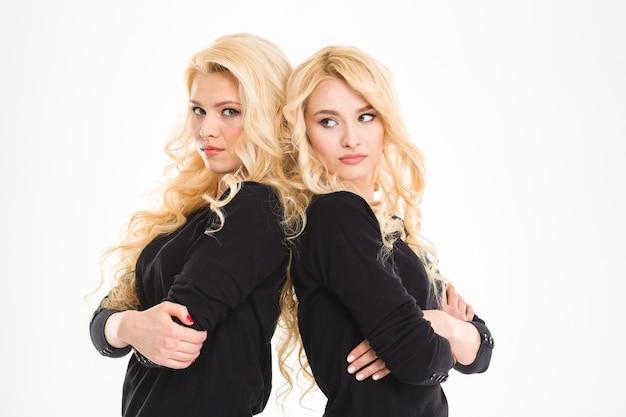 Portret młodych, poważnych bliźniaków sióstr stojących plecami do siebie z założonymi rękoma na białym tle na białym tle