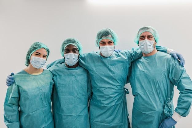 Portret młodych pracowników medycznych patrząc na kamery wewnątrz korytarza szpitala - główny nacisk na prawą twarz człowieka