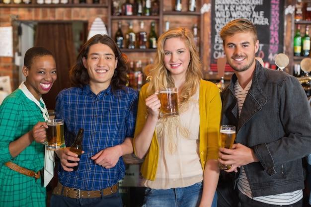Portret młodych przyjaciół trzymając butelki piwa