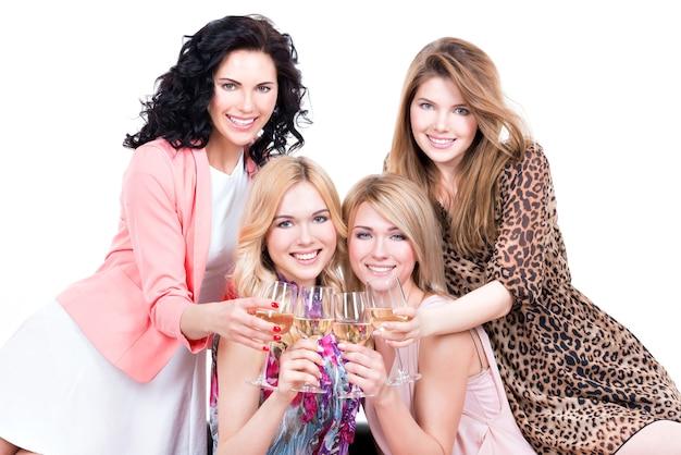 Portret młodych śmiejących się szczęśliwych kobiet siedzi na kanapie z kieliszkami wina - na białym tle