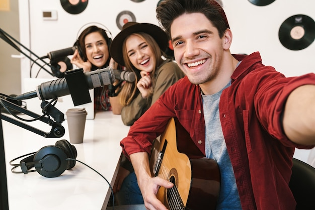 Portret młodych szczęśliwych ludzi rasy kaukaskiej występujących w programie radiowym podczas nagrywania podcastu do programu online