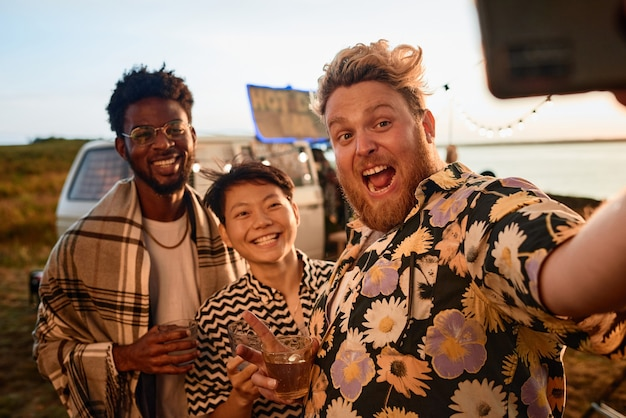 Portret młodych szczęśliwych ludzi uśmiechających się do kamery podczas zabawy na imprezie na świeżym powietrzu